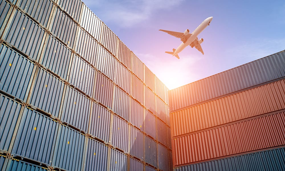 Image of an aeroplane flying over shipping containers