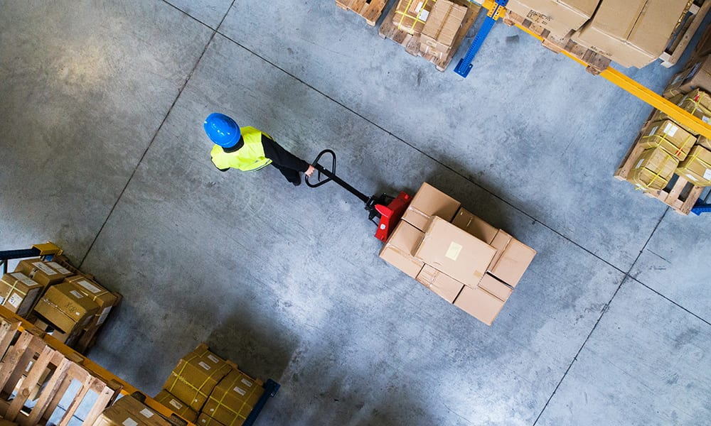 Image of a man using a trolley to transport boxes in a warehouse